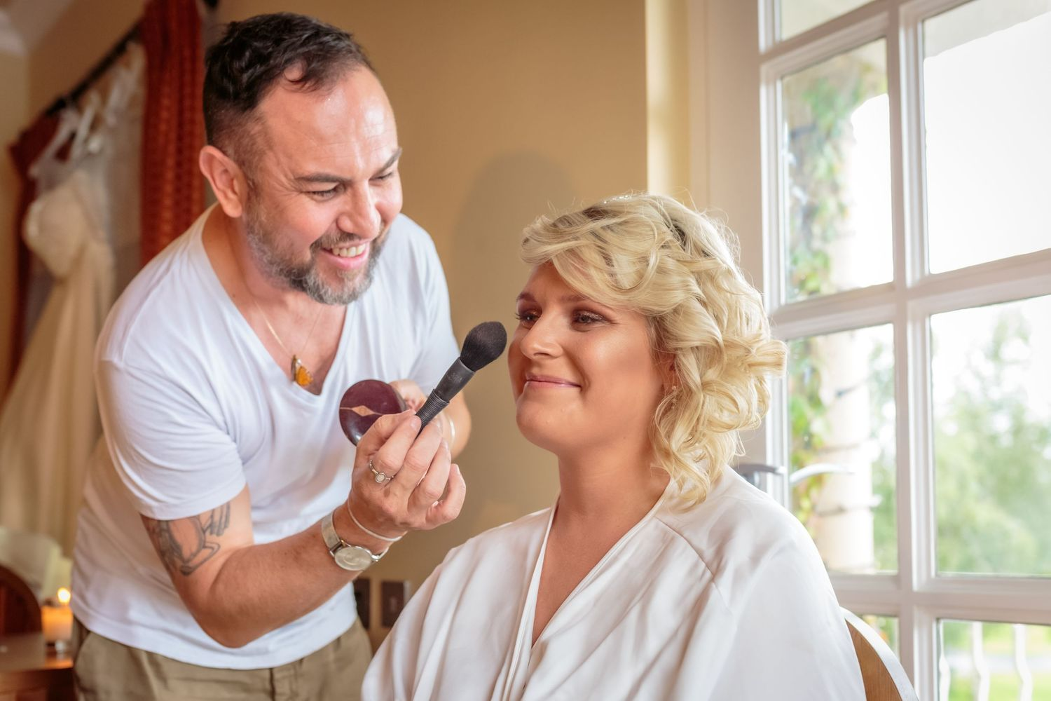 make up artist holding a brush puts the final touches to the bride at ribby hall village