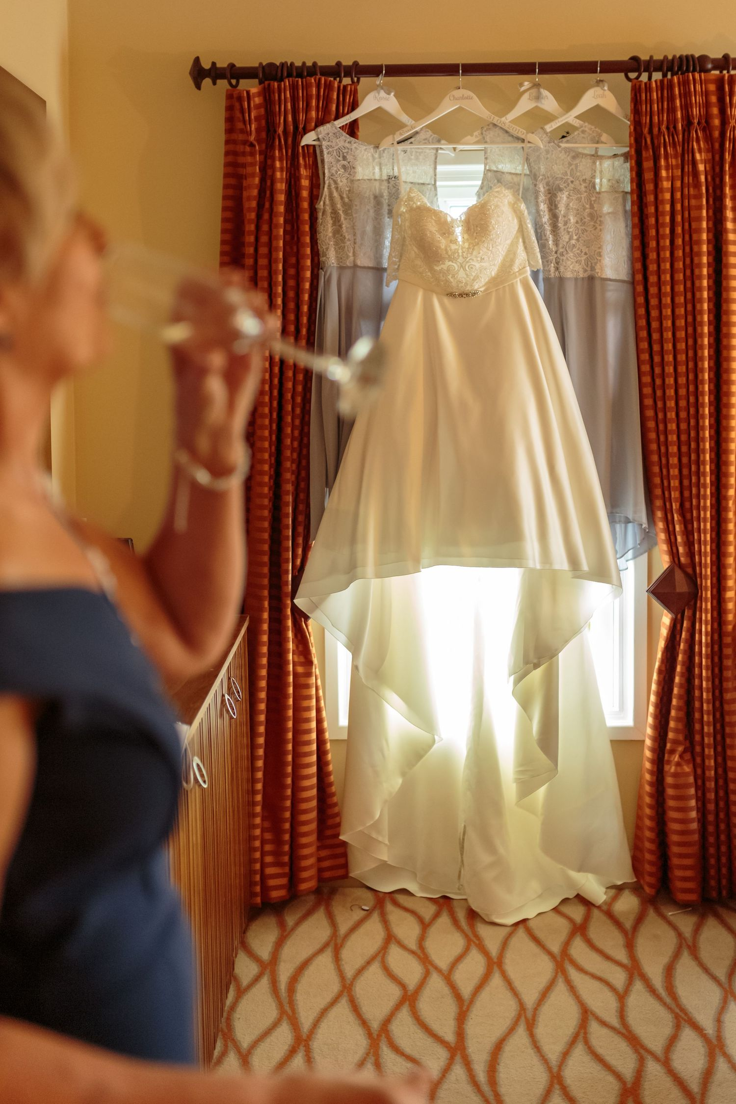 wedding dress hanging up in the window at ribby hall village mother of the bride drink of champagne in the foreground