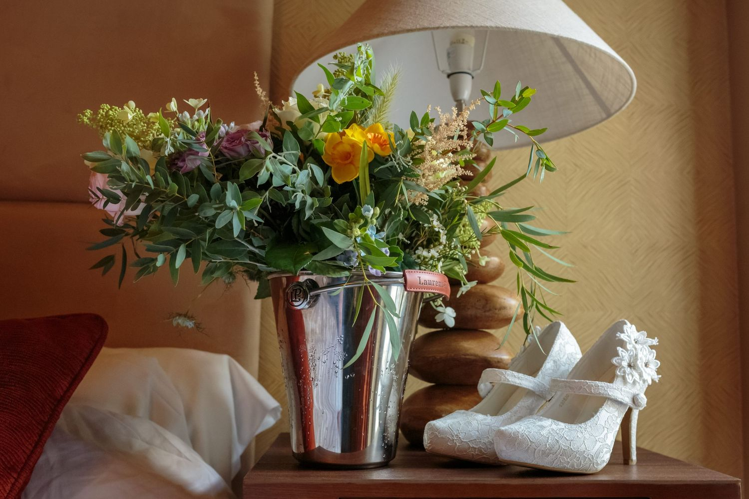 wine bucket with the brides bouquet sitting in it next to her wedding shoes on the bedside table at ribby hall
