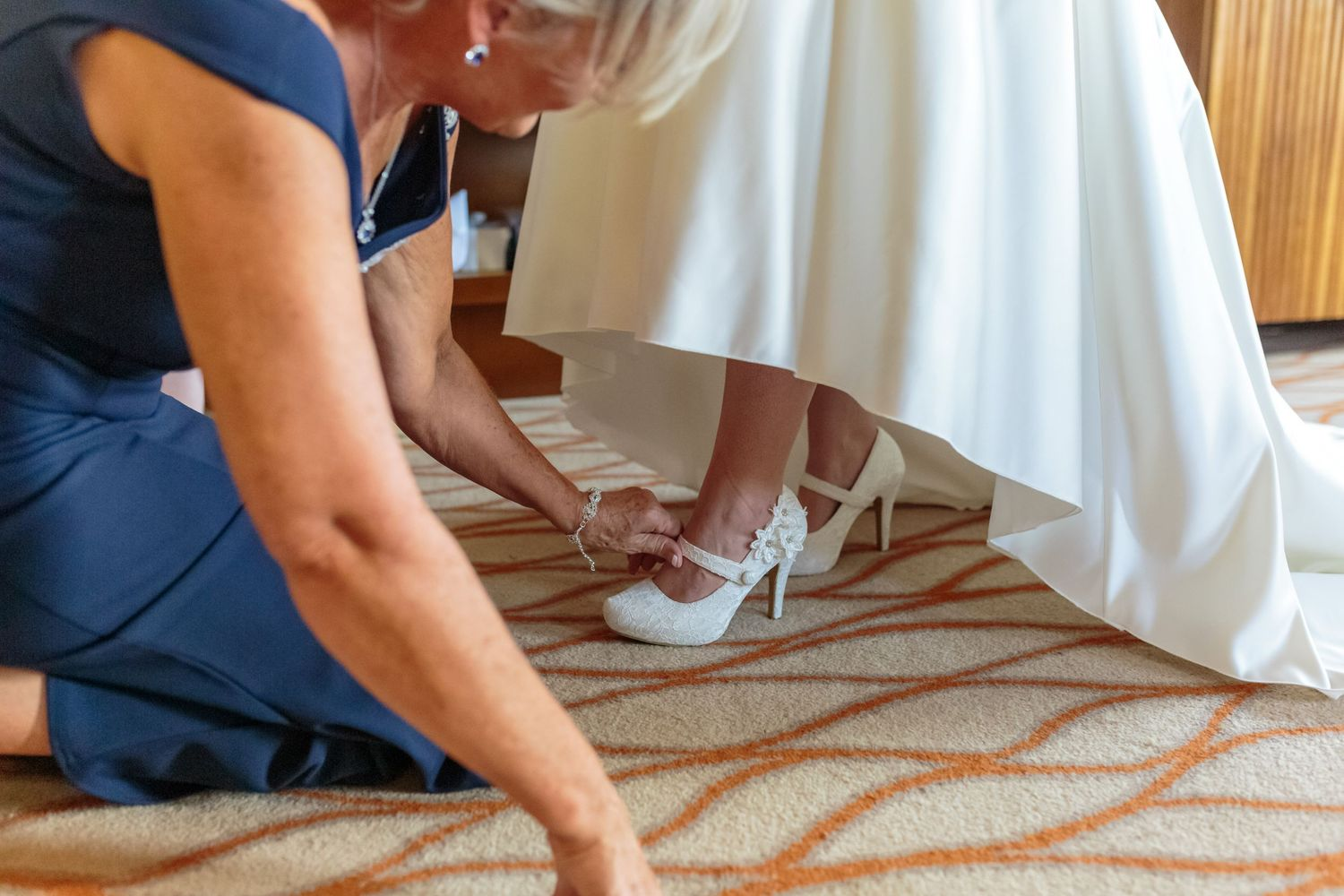 mother of the bride bends down under the dress to fasten the brides shoes