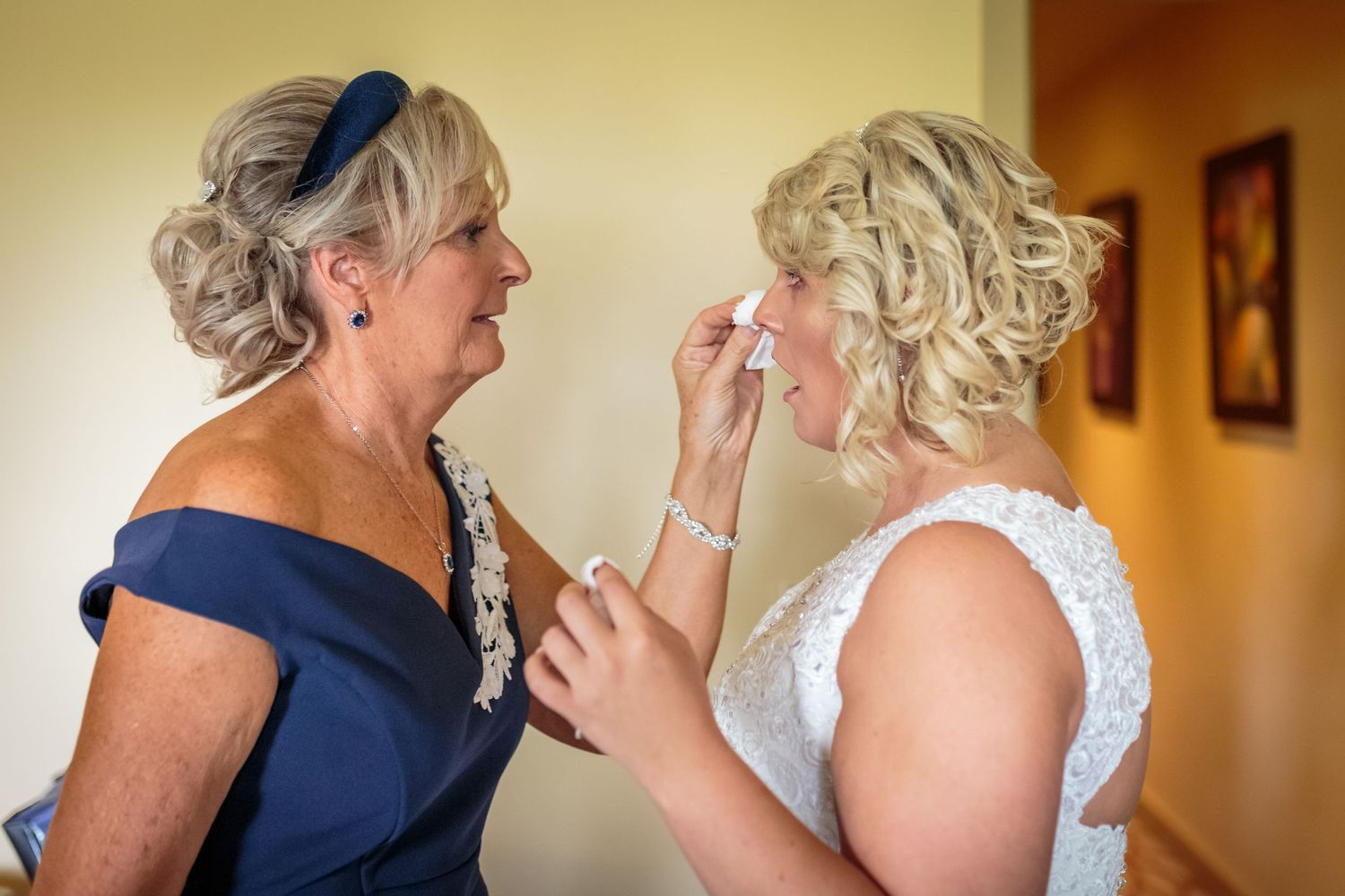 mother of the bride carefully dabs a tear from her daughters eyes so as not to smudge her makeup