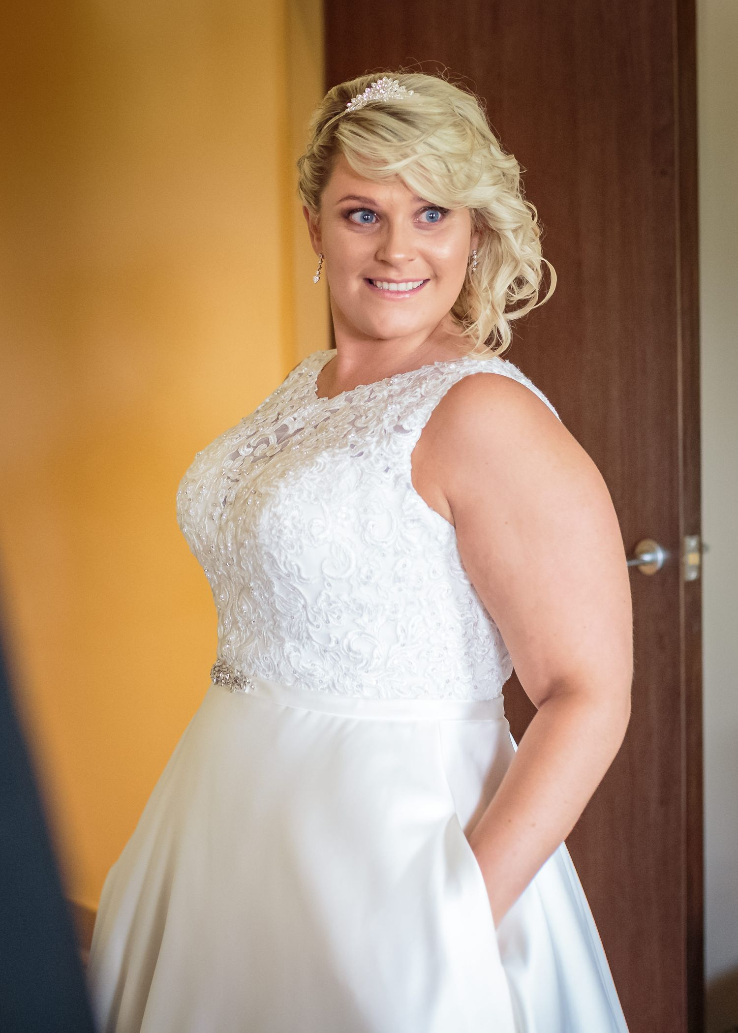 bride smiling with her hands in the pockets of her wedding dress