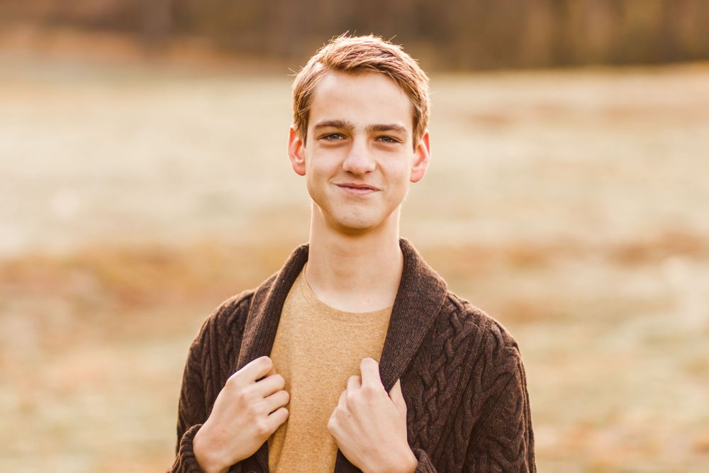 High school senior boy in a sweater smiling up at the camera
