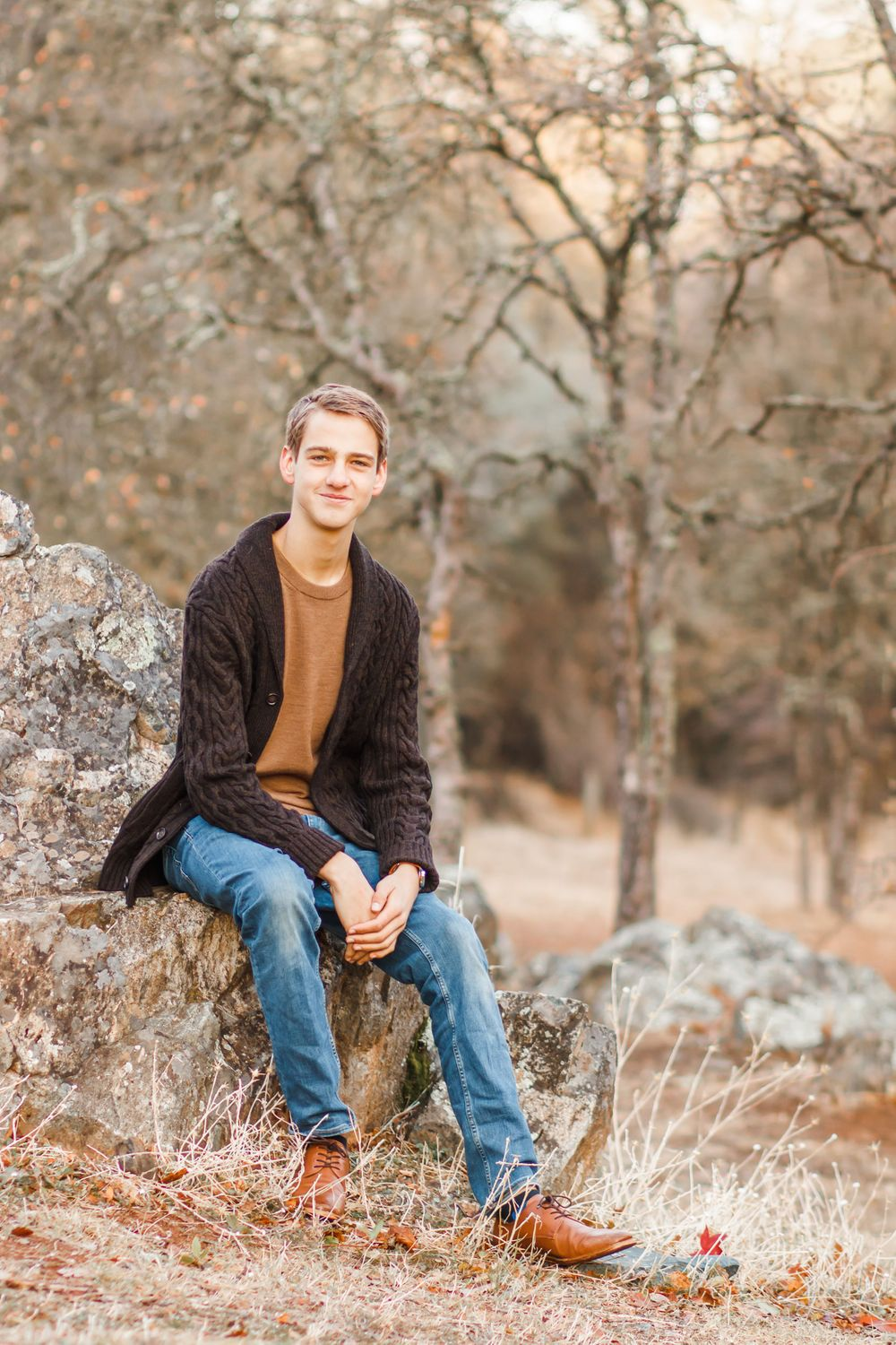 High school senior boy in a sweater and jeans sitting on a rock in a park