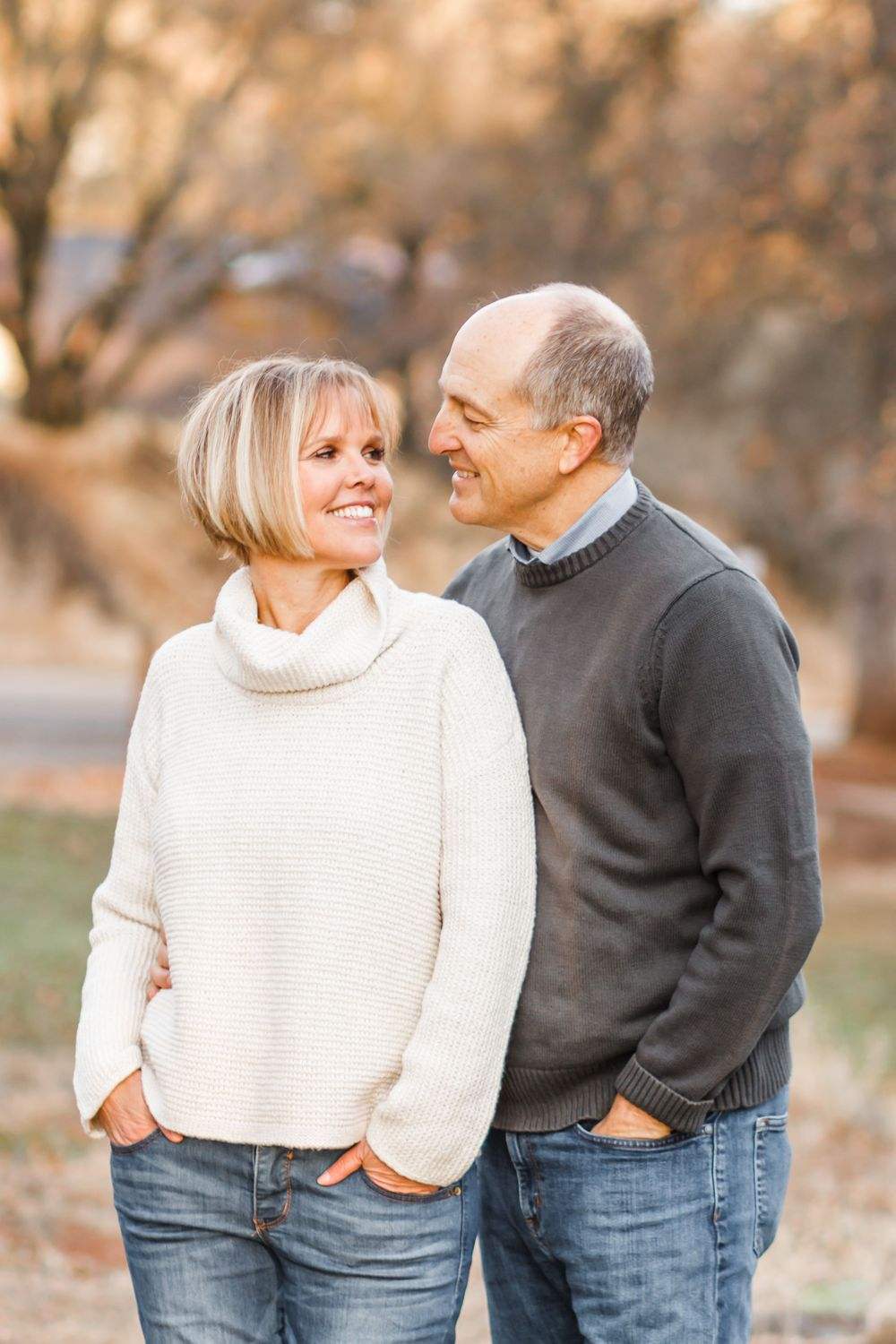 Husband and wife in sweaters turned to look at one another, smiling