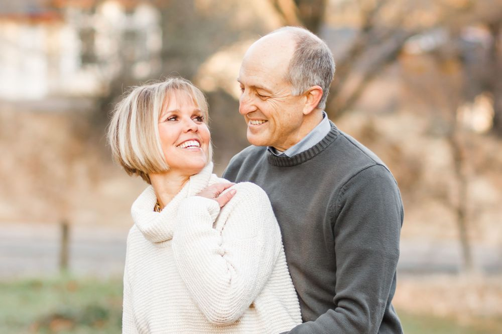 Husband and wife hugging in sweaters turned to look at one another, smiling