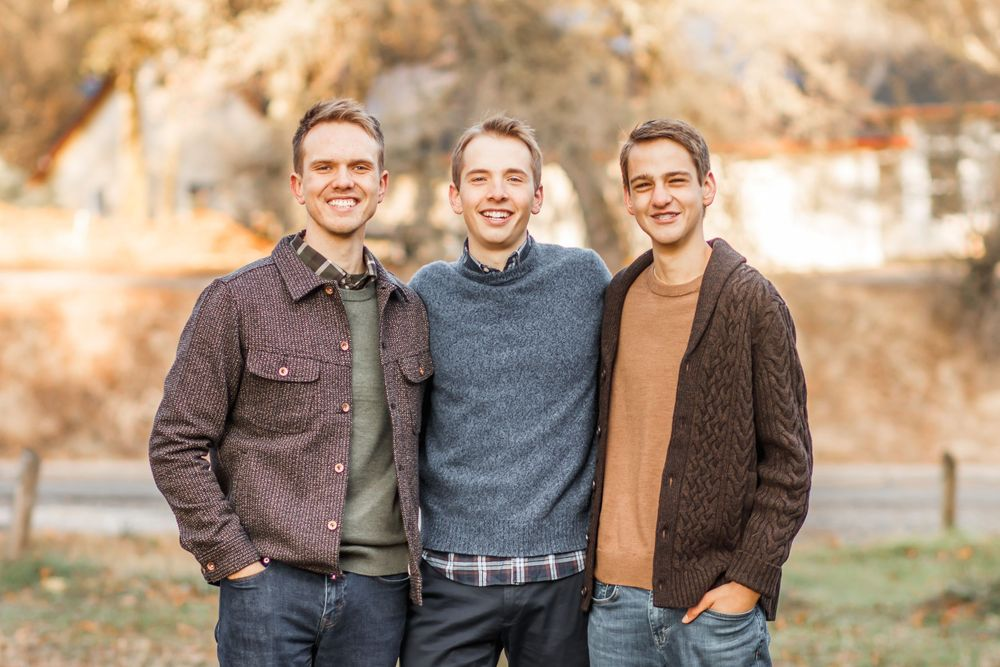 Three brothers with arms around each other smiling in a park