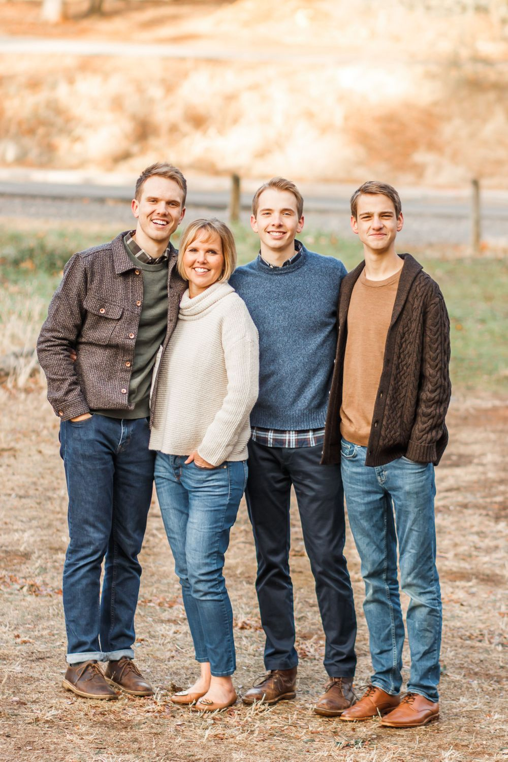 Mother standing with her three sons smiling at the camera