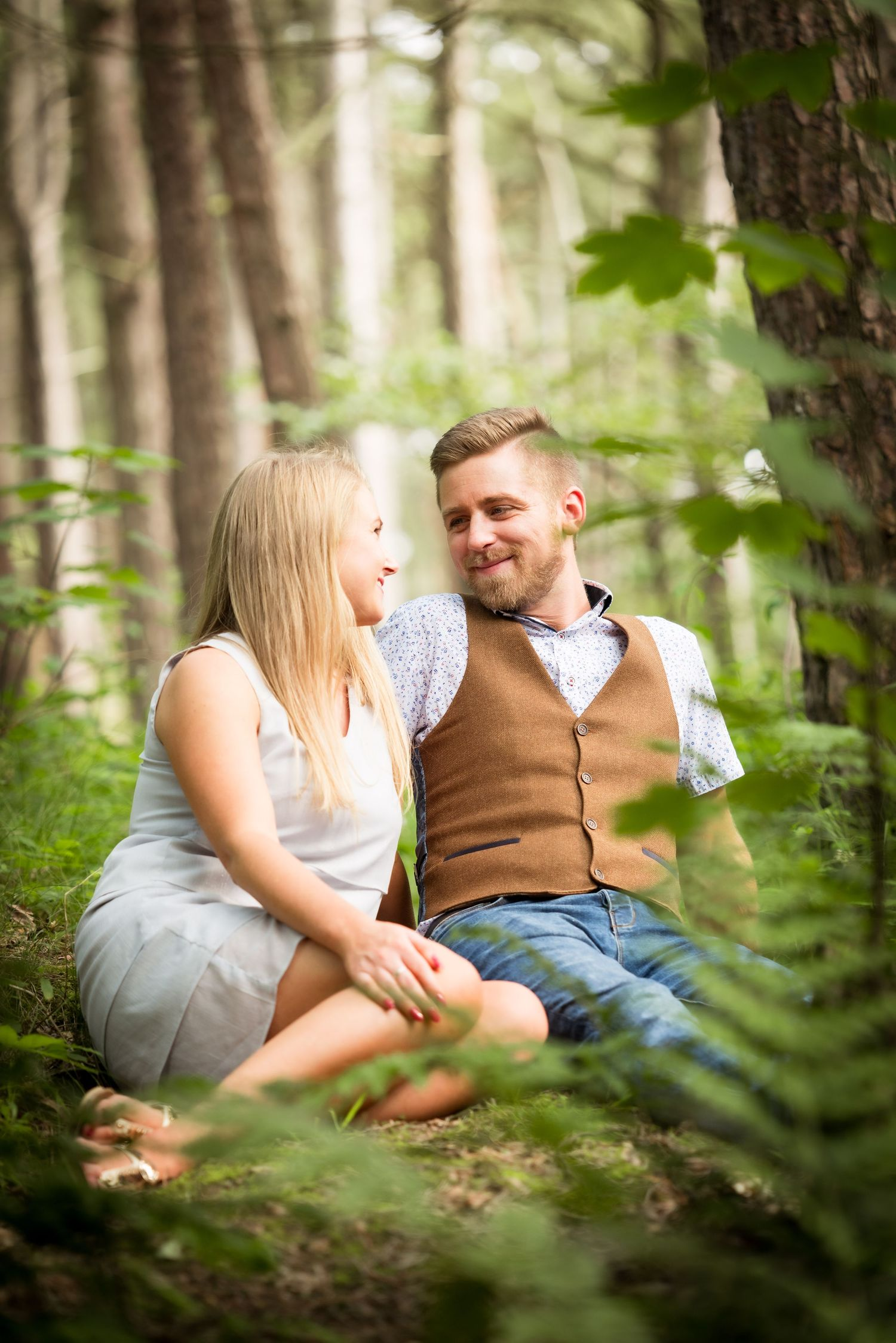 Couple smiling during engagement photoshoot in Formby beach woodland