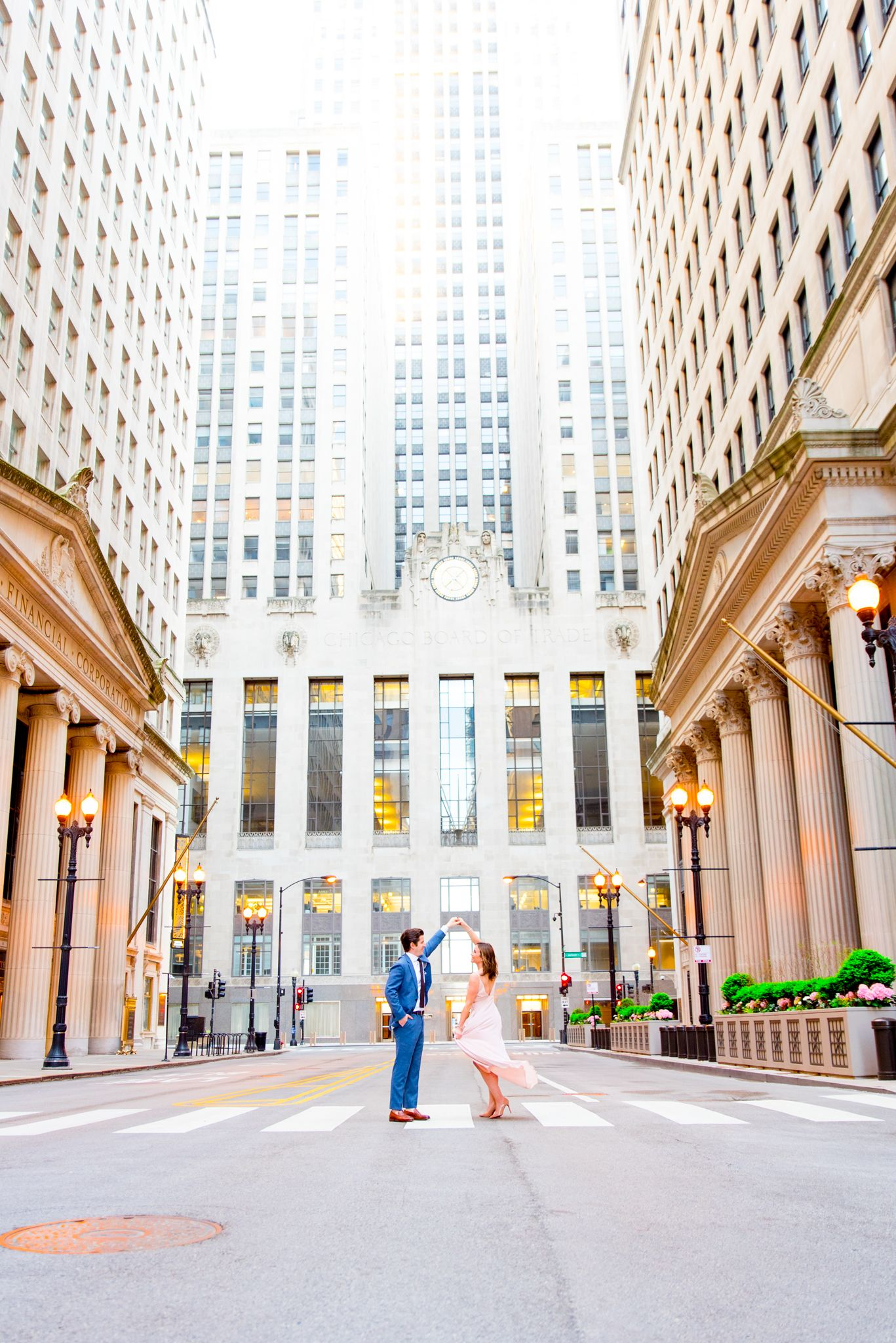 man and woman spin around in front of Chicago Board of Trade at sunset on empty street in downtown Chicago