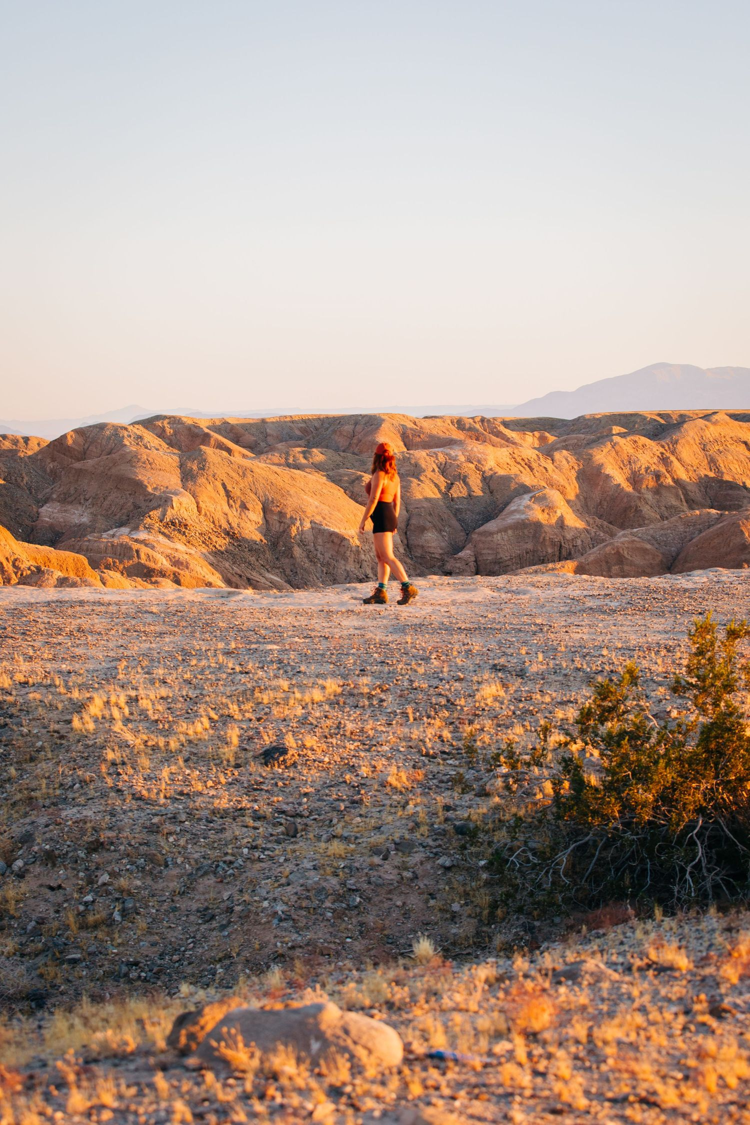 A woman stands at a cliff edge in in the deserts of Southern California.
