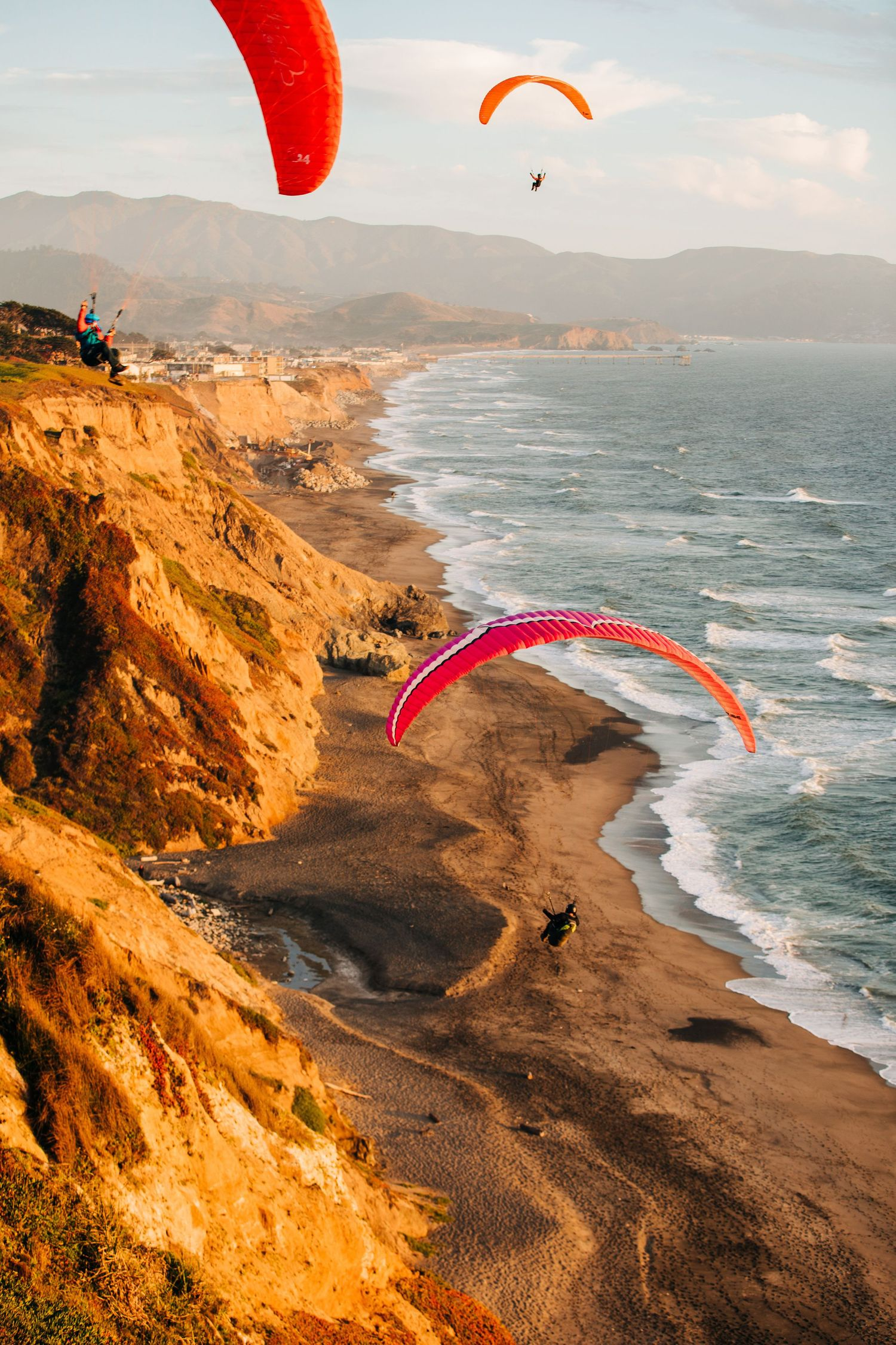 Paragliders travel across the sky over a beautiful beach view in Northern California.
