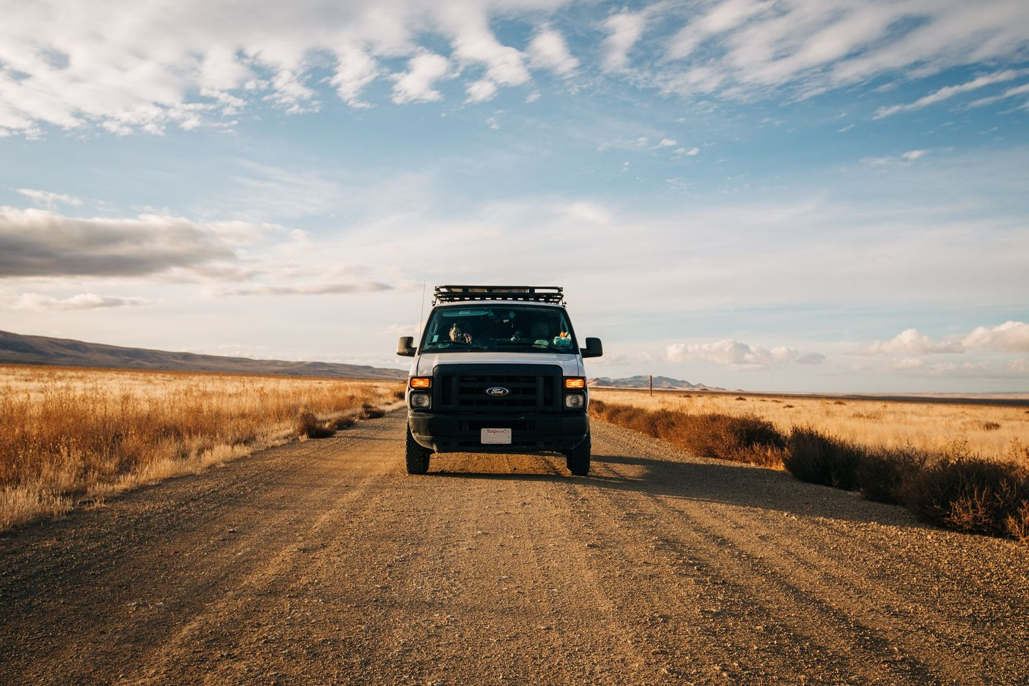 A Ford van stalls on a dirt road on the California plains.