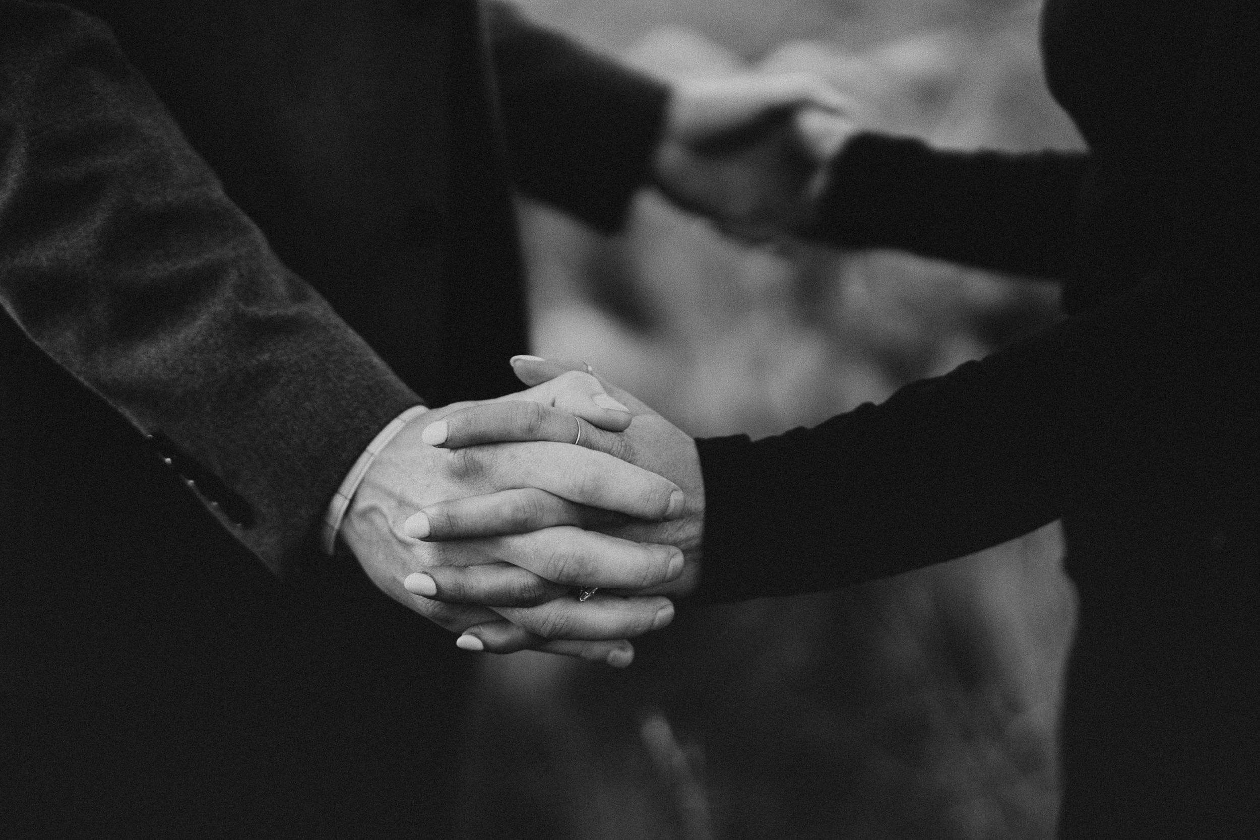 up close black and white image of a couple holding hands