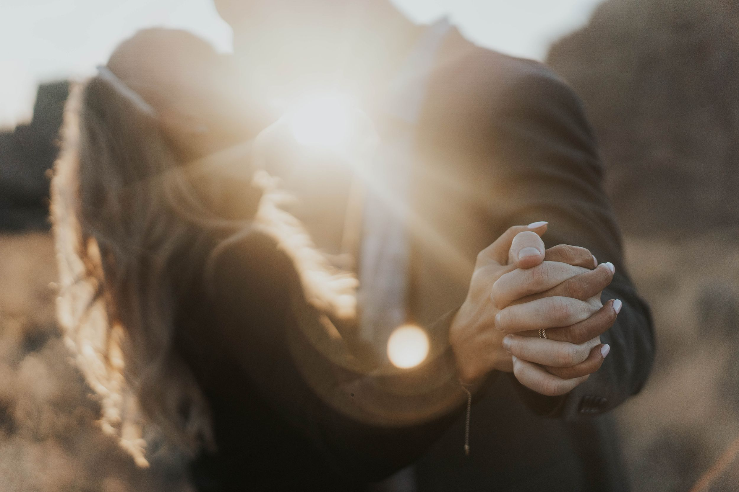 couple holding hands and kissing while the sun shines between them