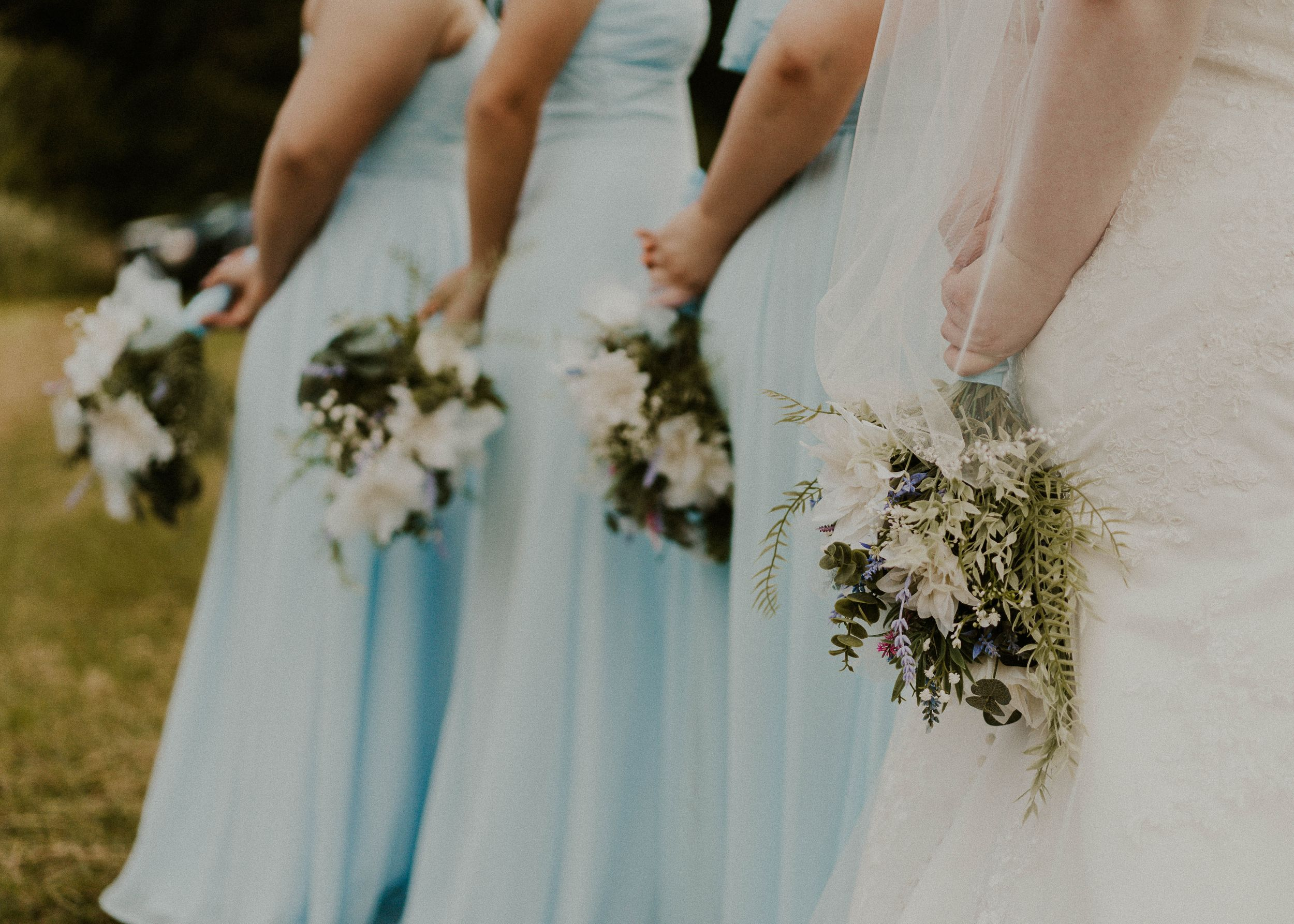 bride and bridesmaids holding their bouquets behind their backs
