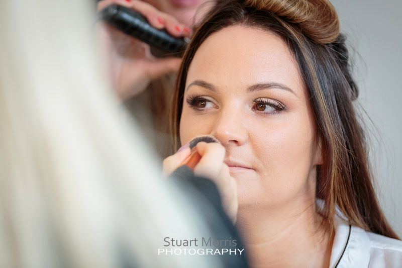 the bride sits still as the hairdresser and makeup artist work on her at the same time