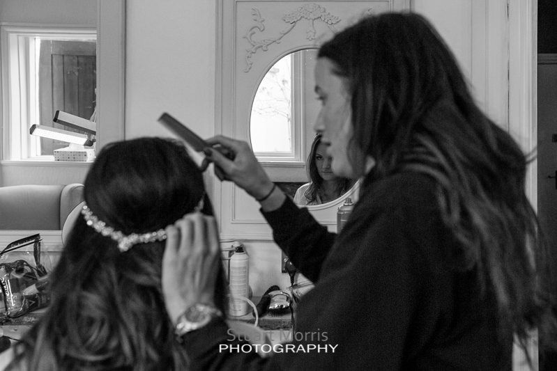 the bride reflected in an oval mirror as the hairdresser woks on her during the prep