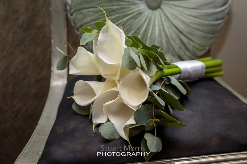 the brides white lillies bouquet sits on a chair during the bridal prep