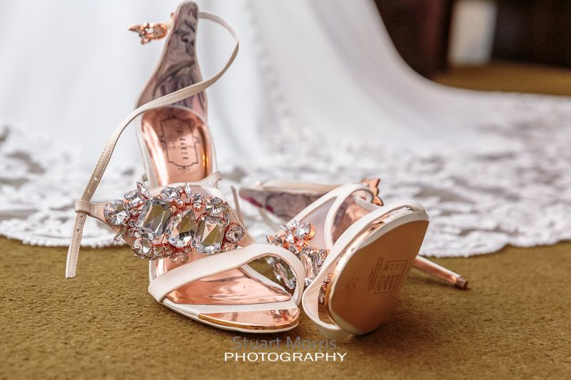 the brides shoes lie on the floor her wedding dress hanging behind them