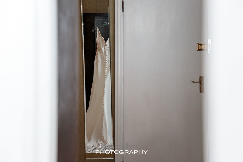 shot through a slightly open doorway of the brides dress hanging from the wardrobe