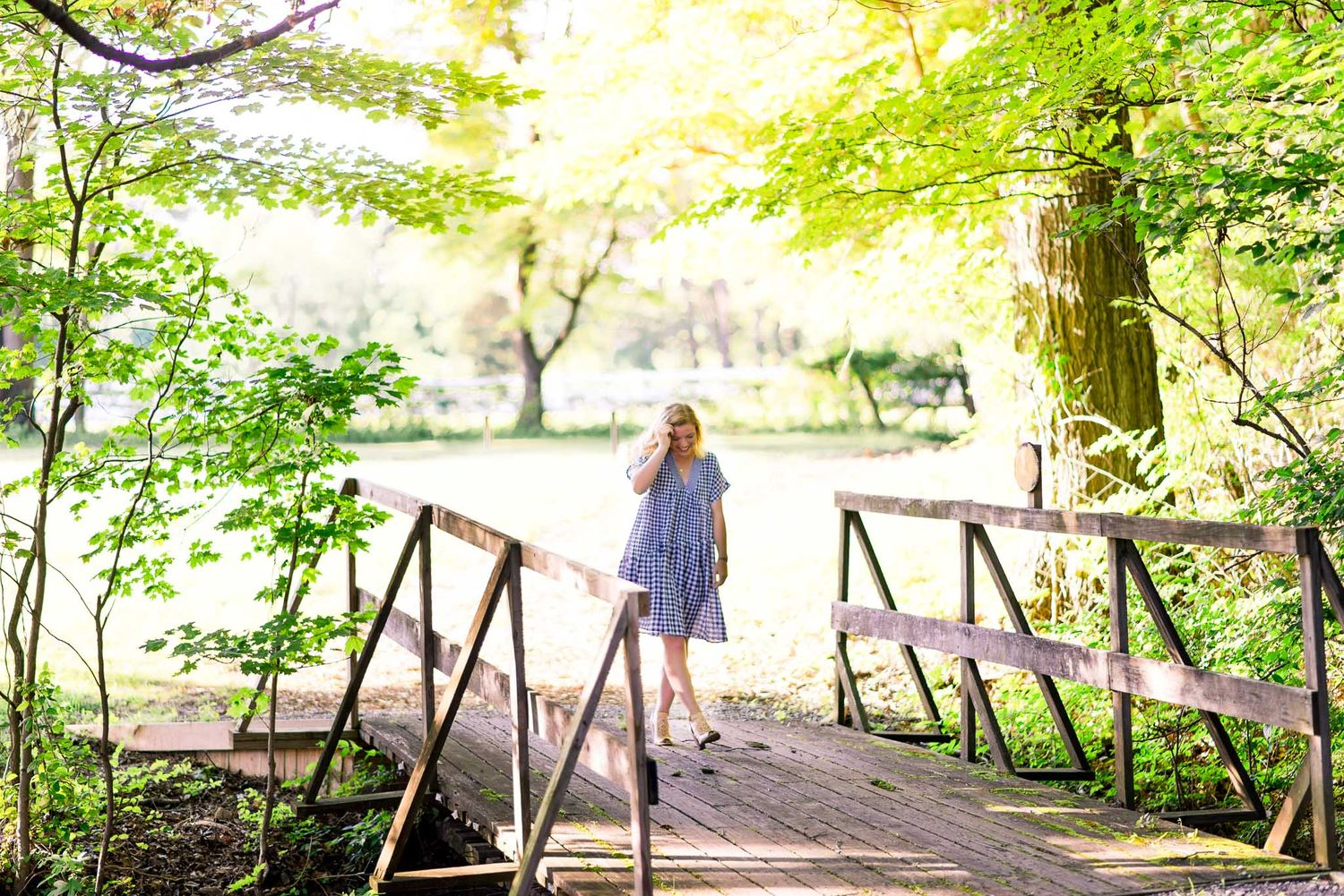 young woman walking across bridge in woods at The Marmalade Lily in Loveland Oh