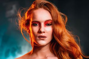 colour gel portrait of red haired woman in red makeup.