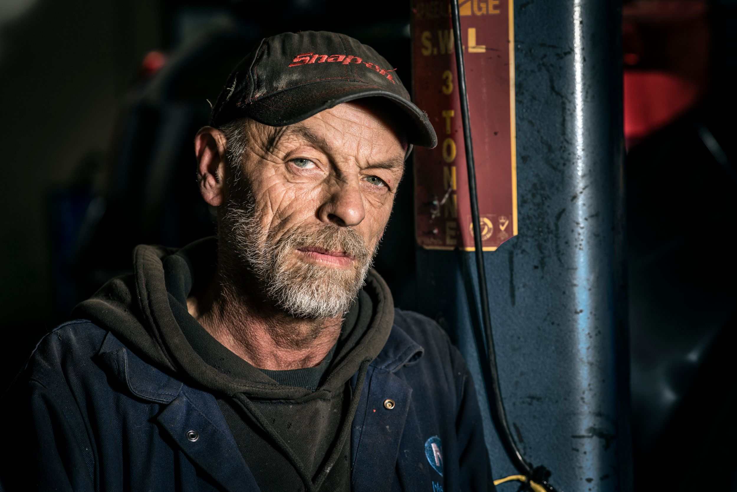 Environmental portrait of mechanic in situ.