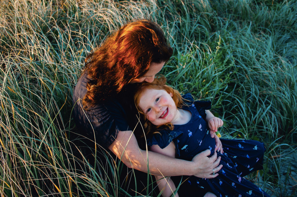 mother and daughter at sunset long grass