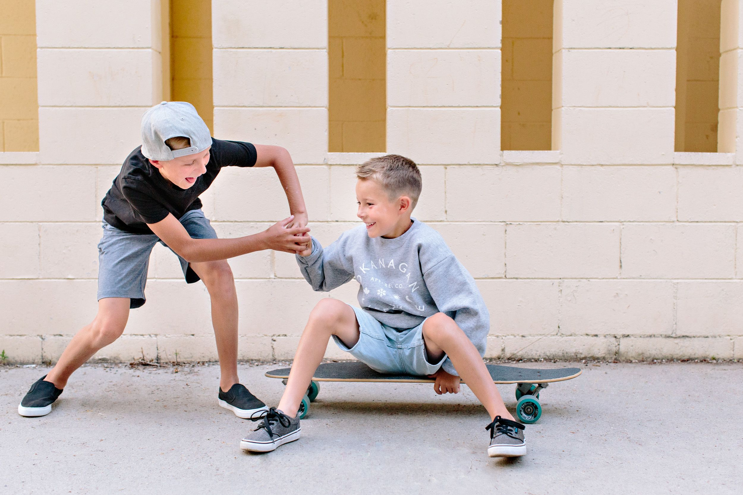 brothers playing around on skateboard