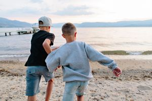 boys running into okanagan lake
