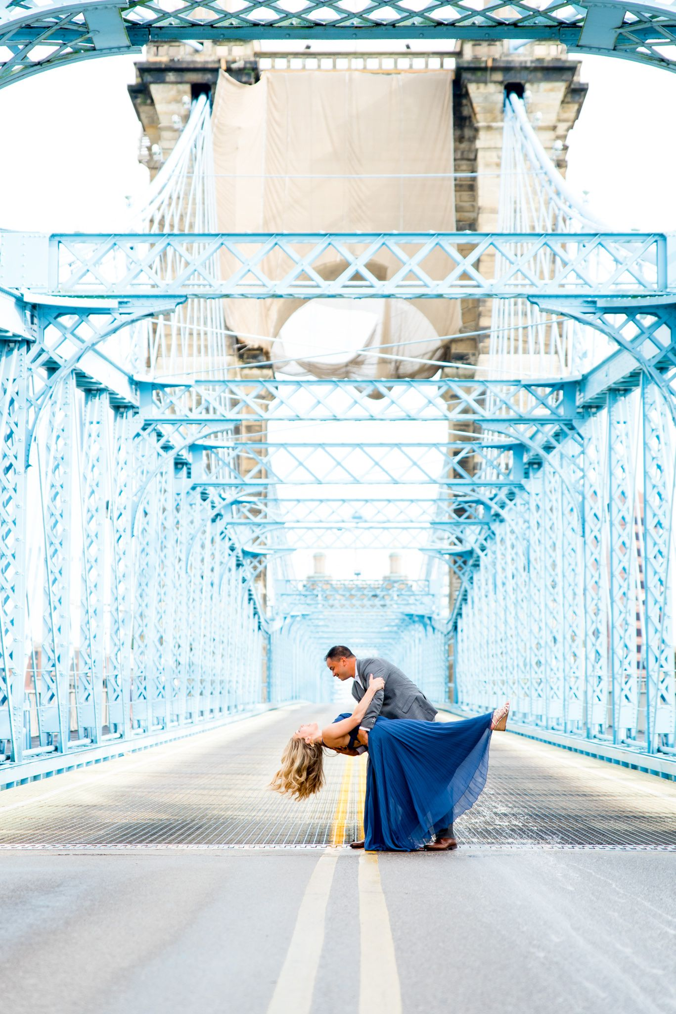 man in gray suit dips woman in blue dress in the middle of Roebling Bridge for Cincinnati engagement pictures