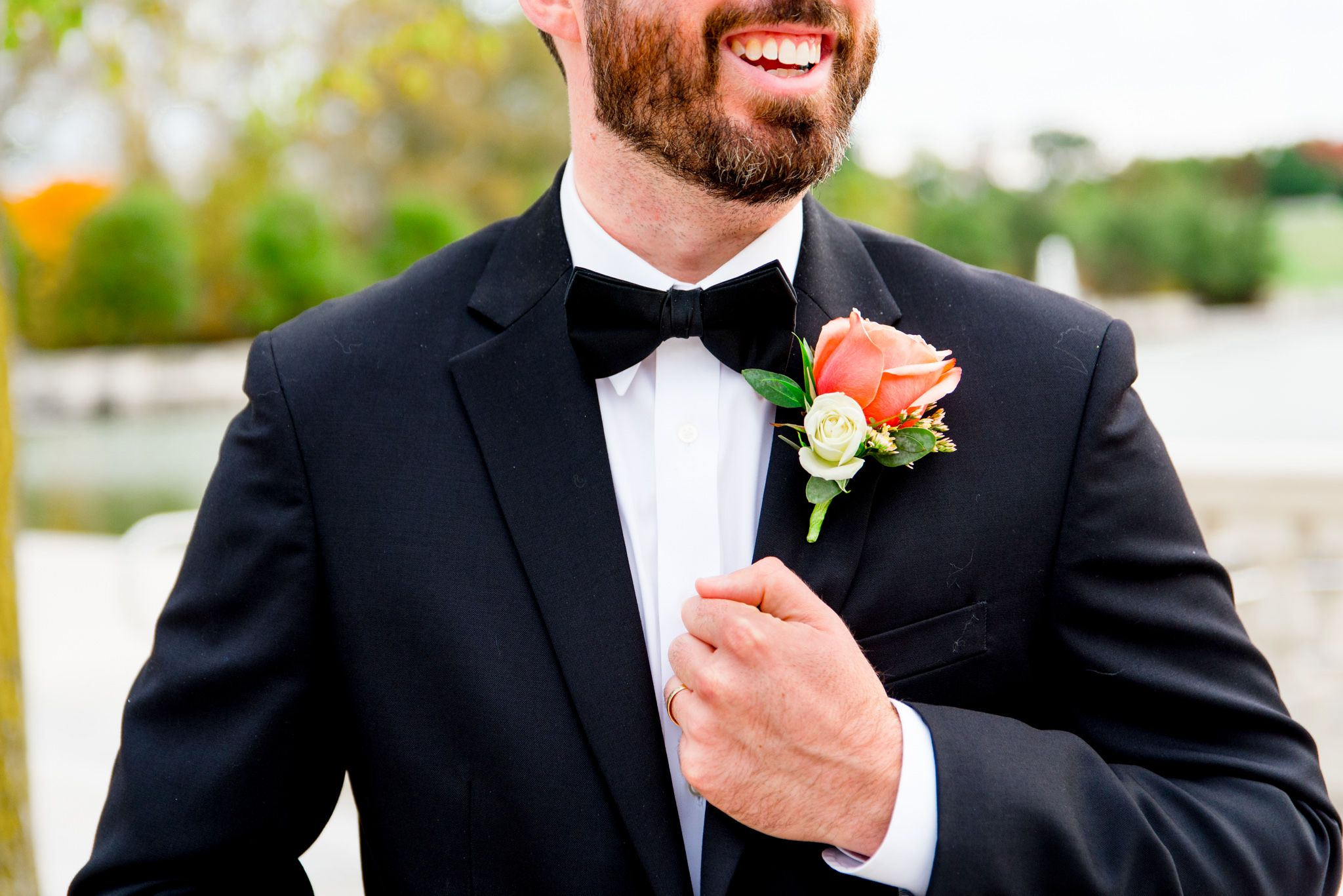 groom's smile and bowtie with coral rose boutonniere showing for St. Louis fall wedding portraits for Chicago couples