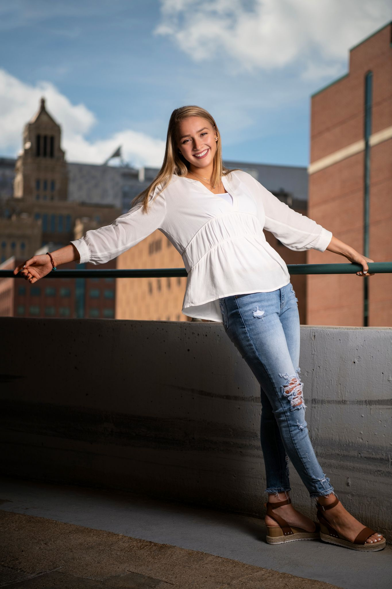 senior girl in white top with torn blue jeans atop parking garage