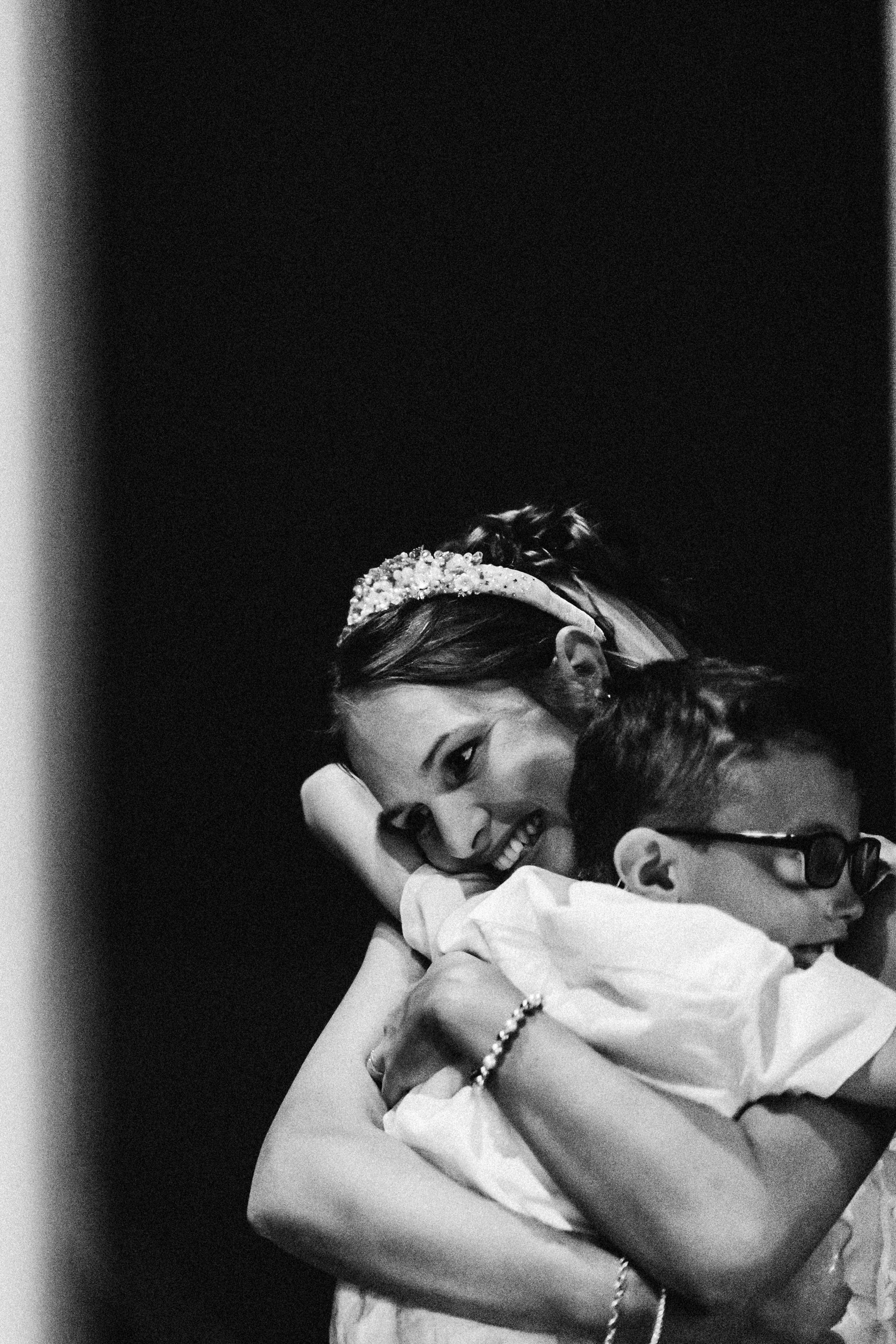 Black and white photograph the bride and pageboy having a big cuddle at 131 cheltenham