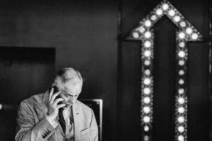 Candid wedding photograph Guest talking on the phone at the Tavern cheltenham with arrow lit up behind him artistic repo