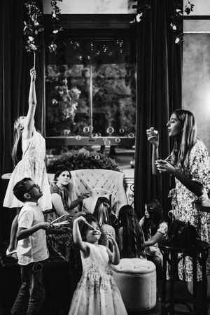 Reportage wedding photograph black and white children blowing bubbles at 131cheltenham