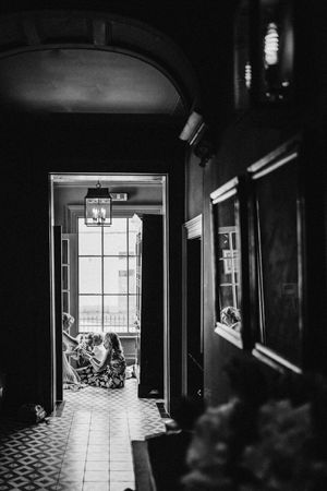 Reportage a black-and-white photograph of bride talking to the pageboy in the hallway at 131 the house