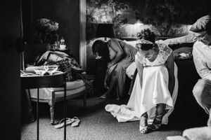 Black and white photograph of the bride getting ready putting her shoes on at 131 cheltenham