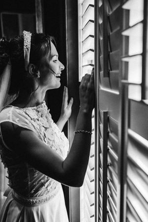 Black-and-white reportage photograph bride looking through the window at guests at 131 Cheltenham