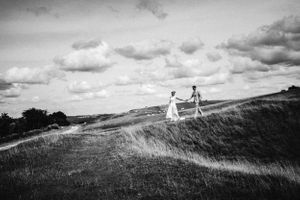 Black and white photograph of bride and groom walking across Cleeve Common hand-in-hand black and white