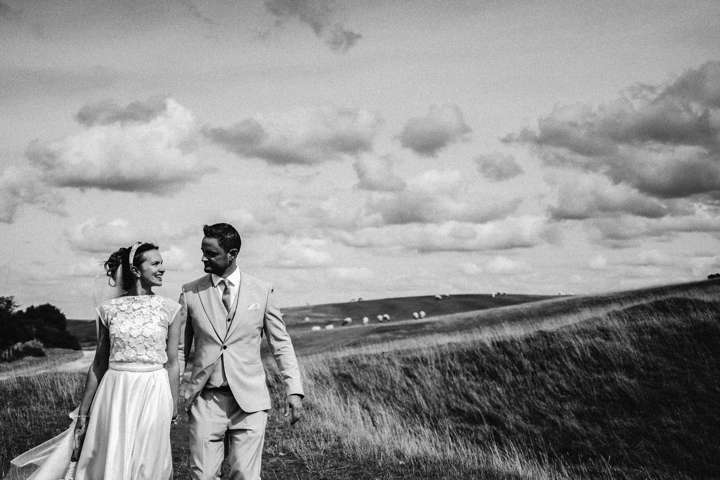 Black and white photograph of bride and groom walking on Cleeve Common holding hands looking at each other