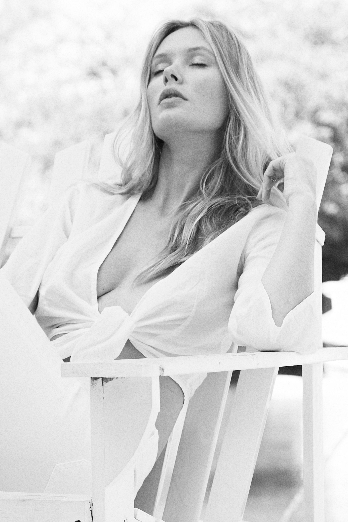 Model Carley Johnston sitting in white rocking chair on a porch South Beach, Miami