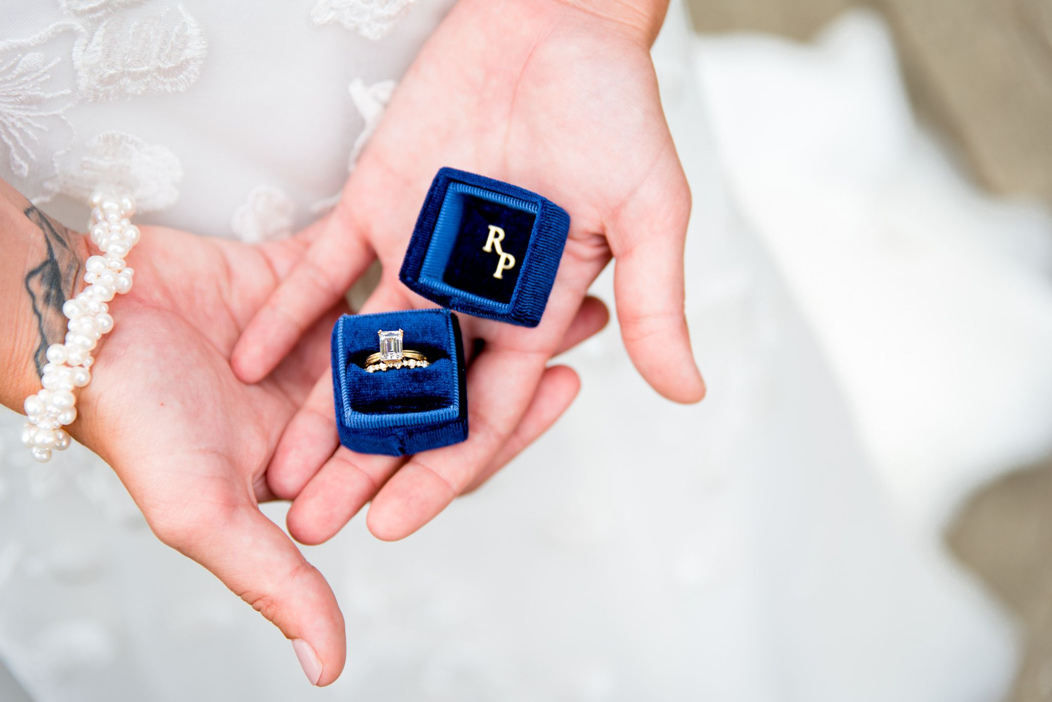 bride with wrist tattoo and pearl bracelet holding blue ring box with emerald cut diamond ring inside