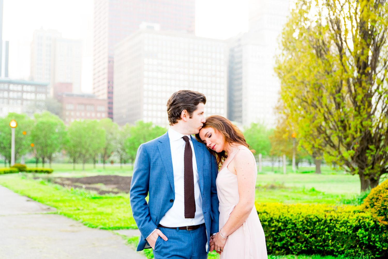 man in Navy suit kissing fiancee in pink dress on forehead in Chicago Grant Park for sunset engagement pictures
