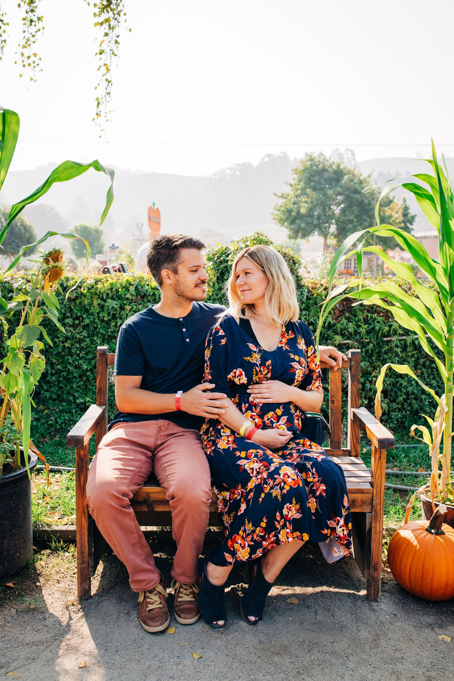 A camera-shy expecting couple sits together in a pumpkin patch in northern California.