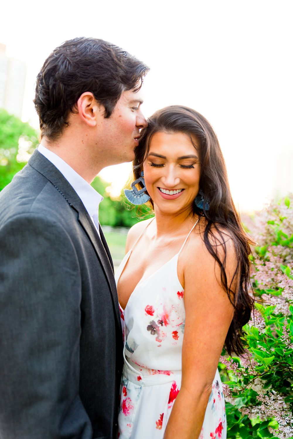 man in gray suit kissing woman in floral dress and blue earrings at sunset while she smiles for engagement pictures