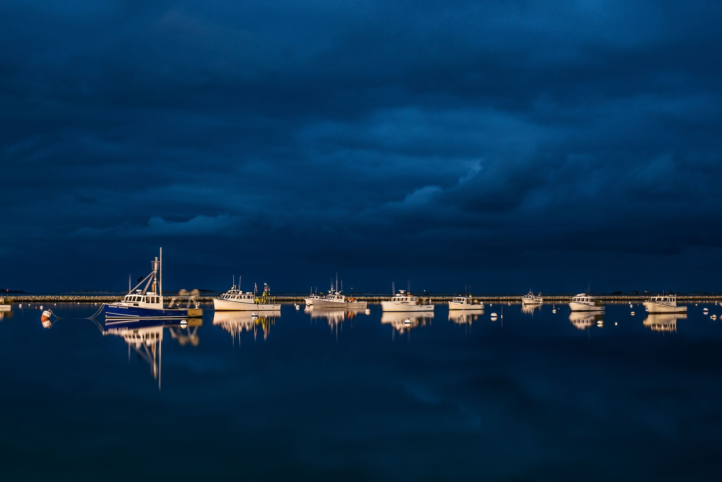 Night landscape of Plymouth Harbor filled with boats