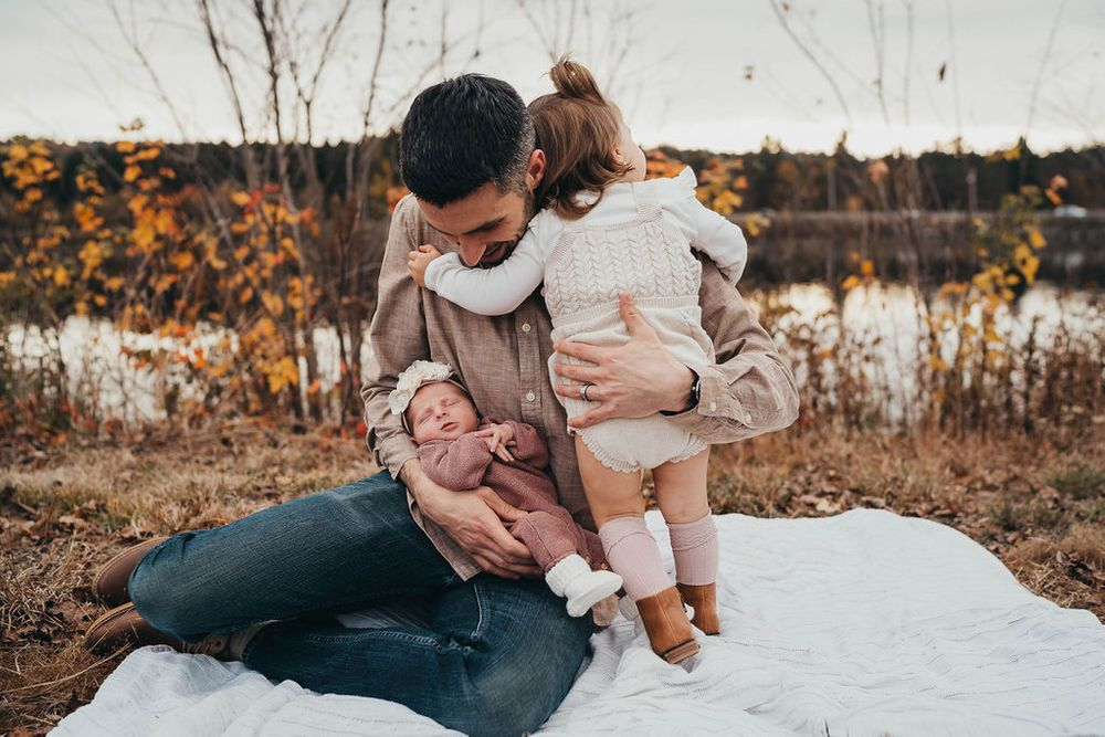 toddler hugging dad while holding newborn in boston massachusetts