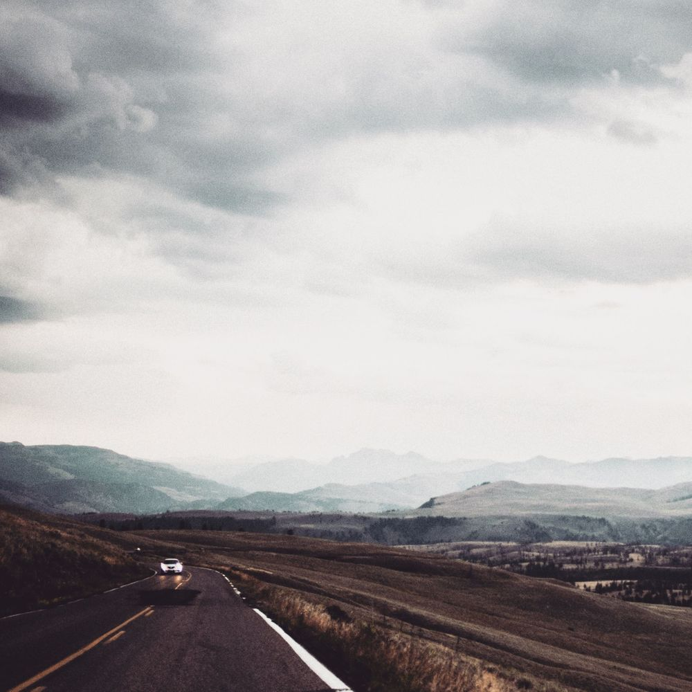 picture of road and car in the distance during a cloudy day at yellowstone national park, wyoming